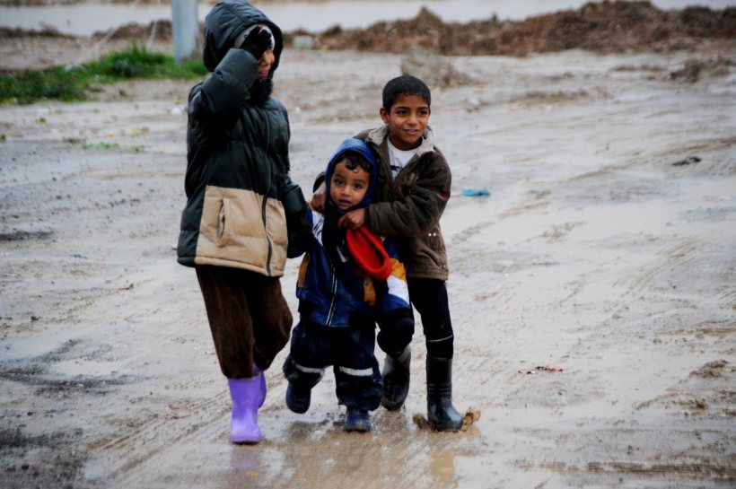 ARBIL, IRAQ - DECEMBER 14: Iraqi refugee children, fled their homes due to the violence of armed groups led by Islamic State of Iraq and Levant (ISIL) in Mosul and Tal Afar, play in the mud after the rain at Baharka refugee camp in Erbil, Iraq on December 14, 2014. Rain and winter worsens the living conditions of Iraqi refugees staying in the tents. (Hamit Hüseyin - Anadolu Agency)